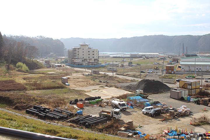 現在の田老町。高台の斜面を削って新たな町が作られています。 遠くに津波の被害を受けた「たろう観光ホテル」が確認できます。