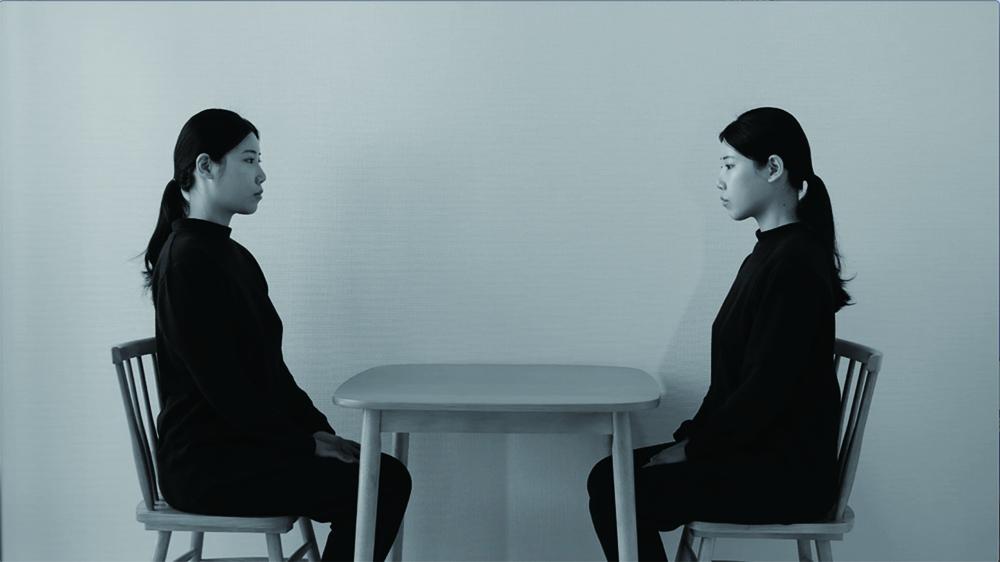 カン ミンハ 「カンミンハはテーブルの向こうに座っている」 映像、プロジェクター、DVD プレーヤー、スピーカー サイズ可変